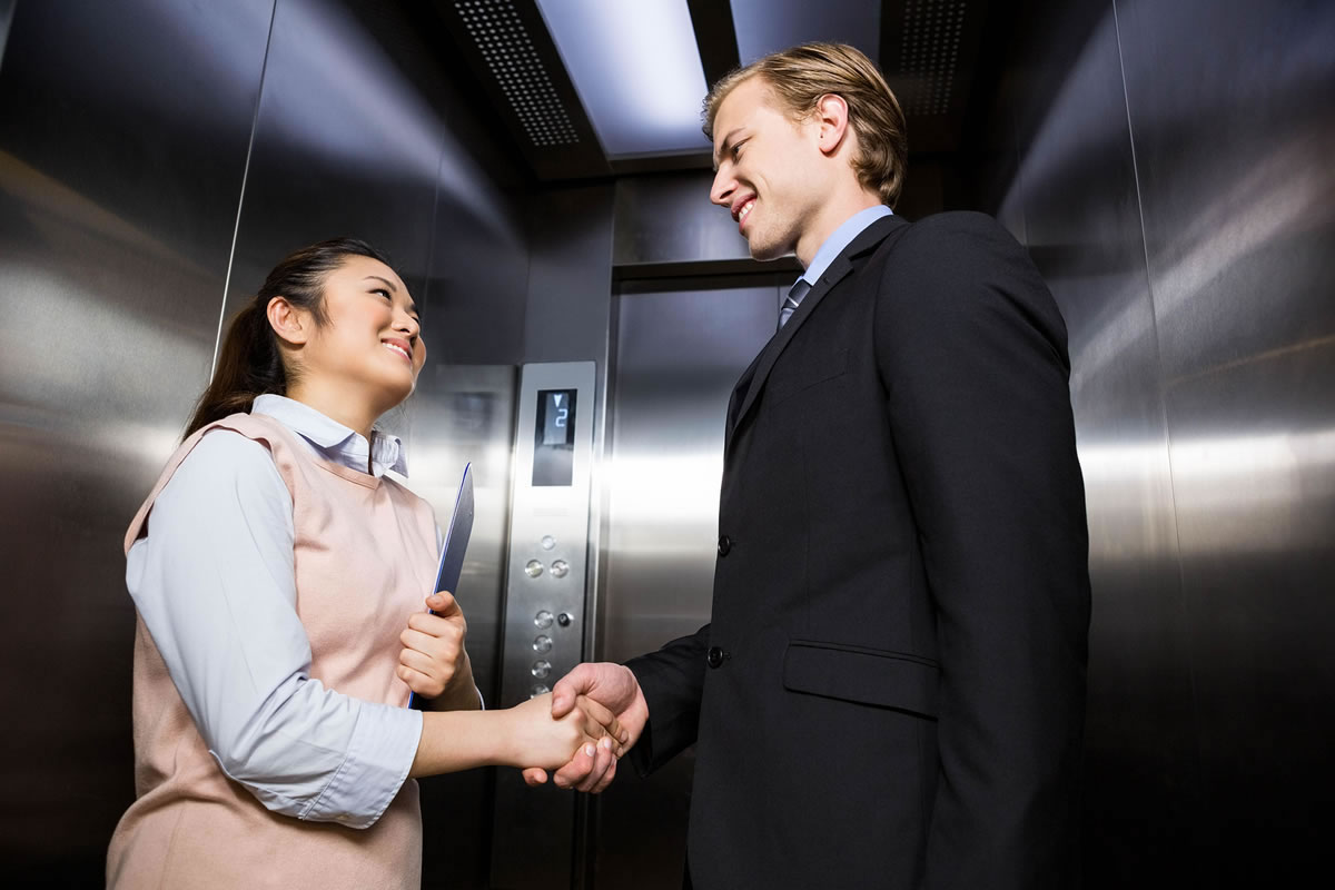 Woman and man in elevator smiling and shaking hands