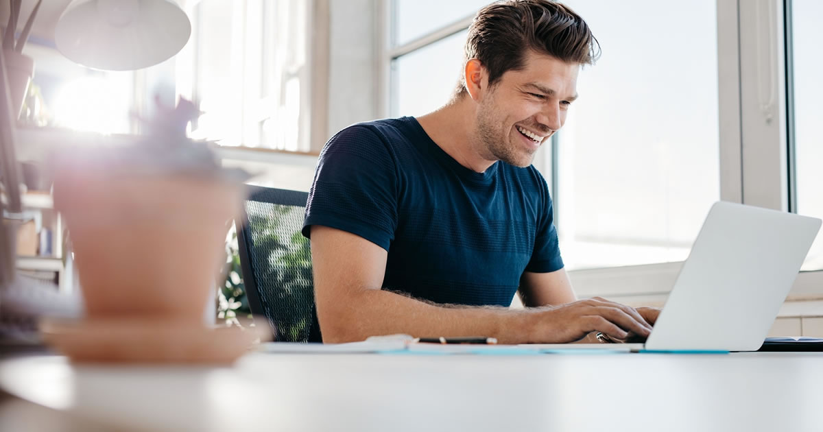 Smiling man sitting at a table using a laptop