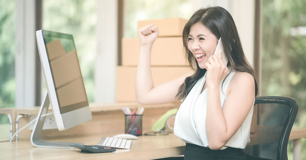 Woman on phone cheering at desk