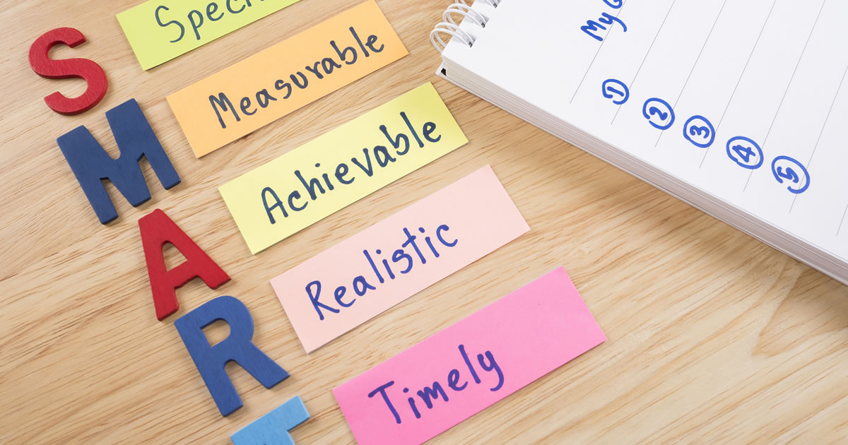 Notes on a desk with the words specific, measurable, achievable, realistic, and timely