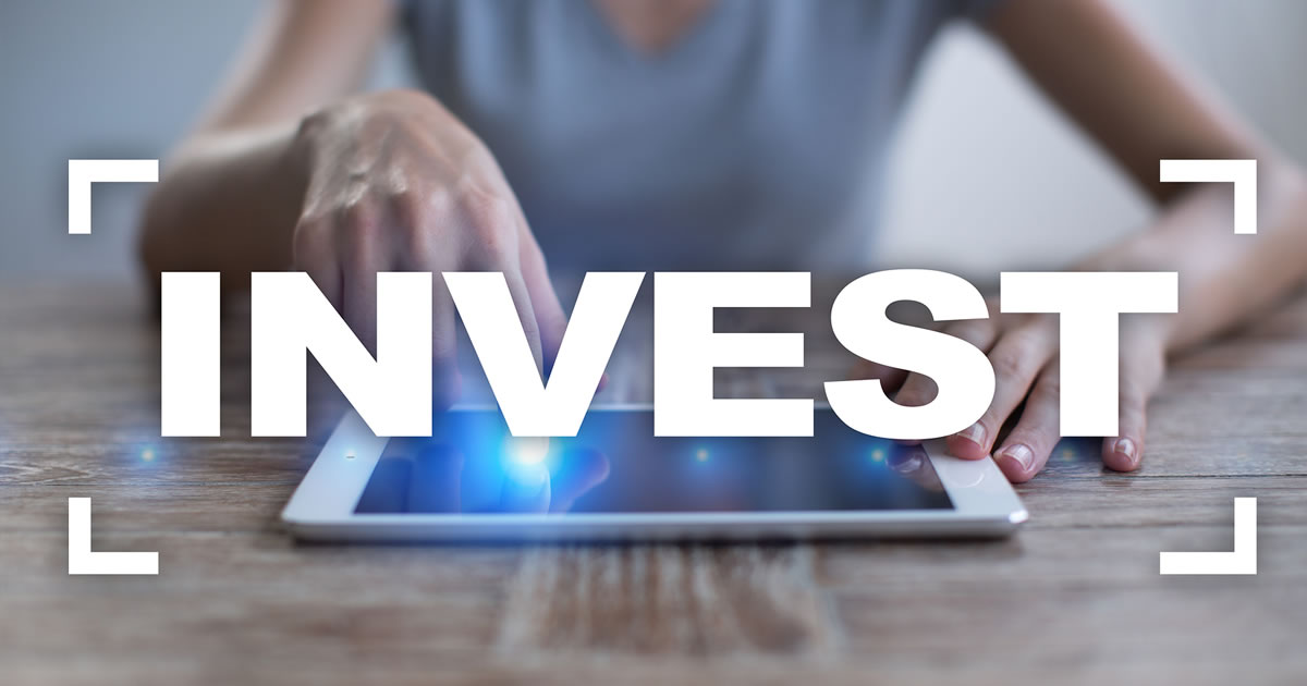The word invest over a photo of person's hands using a tablet