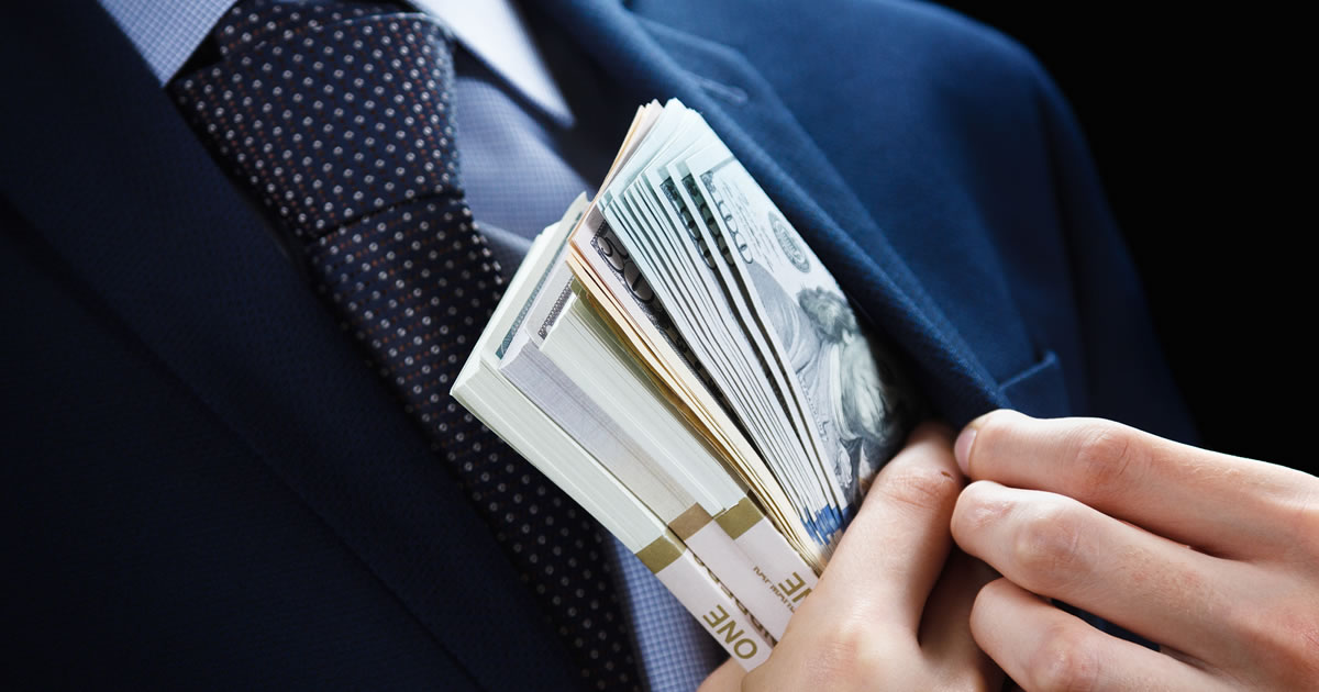 Closeup of hands tucking stacks of cash into suit jacket inside pocket