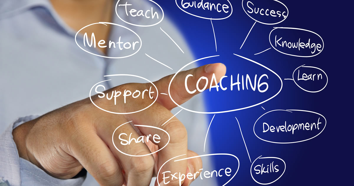 Person pointing to display of the word coaching surrounded by related terms such as mentor, teach, and success