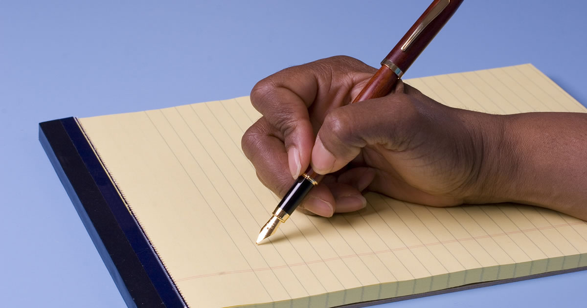 A hand holding a pen to a pad of paper