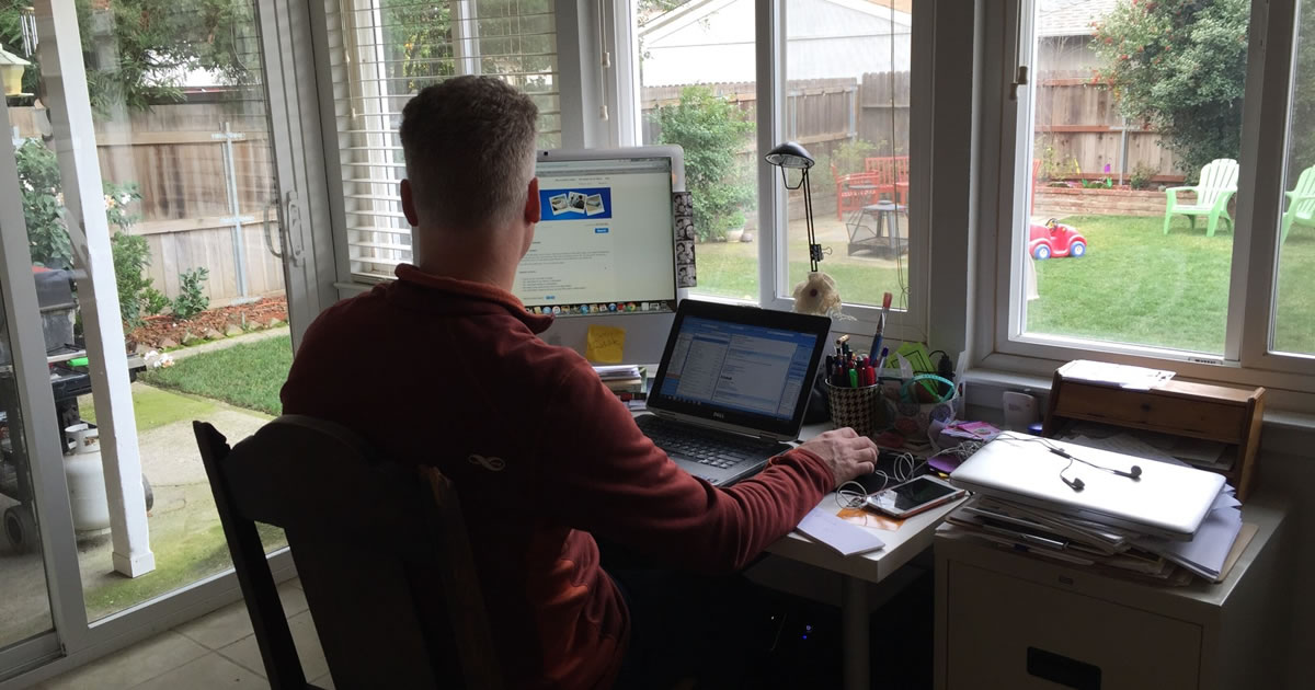 Man sitting in front of computer at desk in home office with view of his backyard