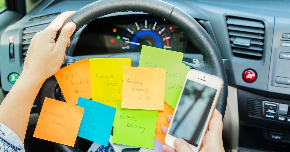 Person in car driver's seat with mobile phone and steering wheel covered in to do list sticky notes