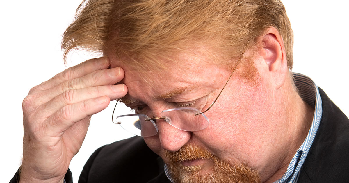 Close-up of man looking down with his hand to his forehead