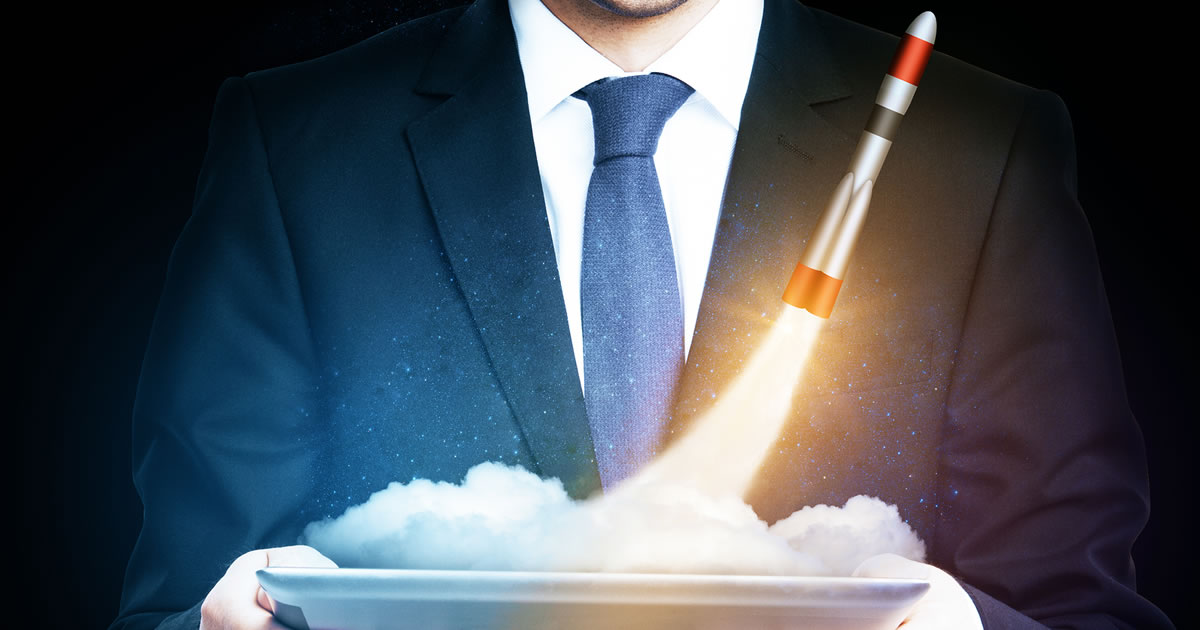 Business person holding tablet with graphic of a rocket launching out of it