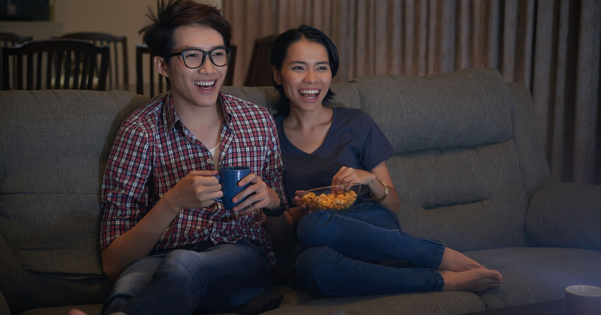 Two smiling people with drink and snack sitting together on couch watching television