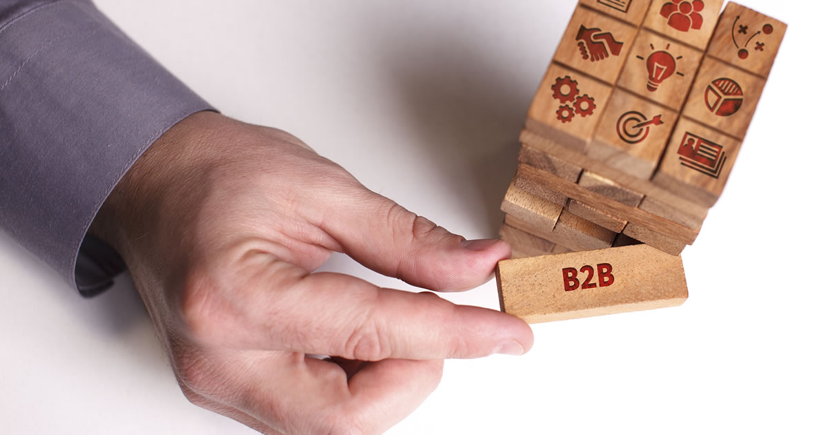 Person's hand removing a wooden block with the word B2B on it from a stack of blocks