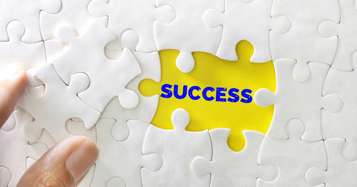 White jigsaw puzzle with two pieces missing over the word success