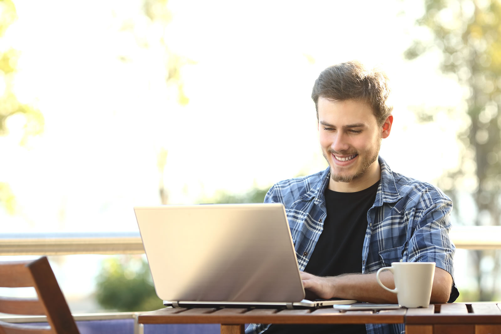 Smiling man at table working on laptop