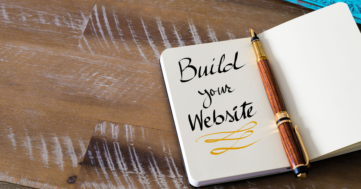 Fountain pen and the words build your website written on a journal page