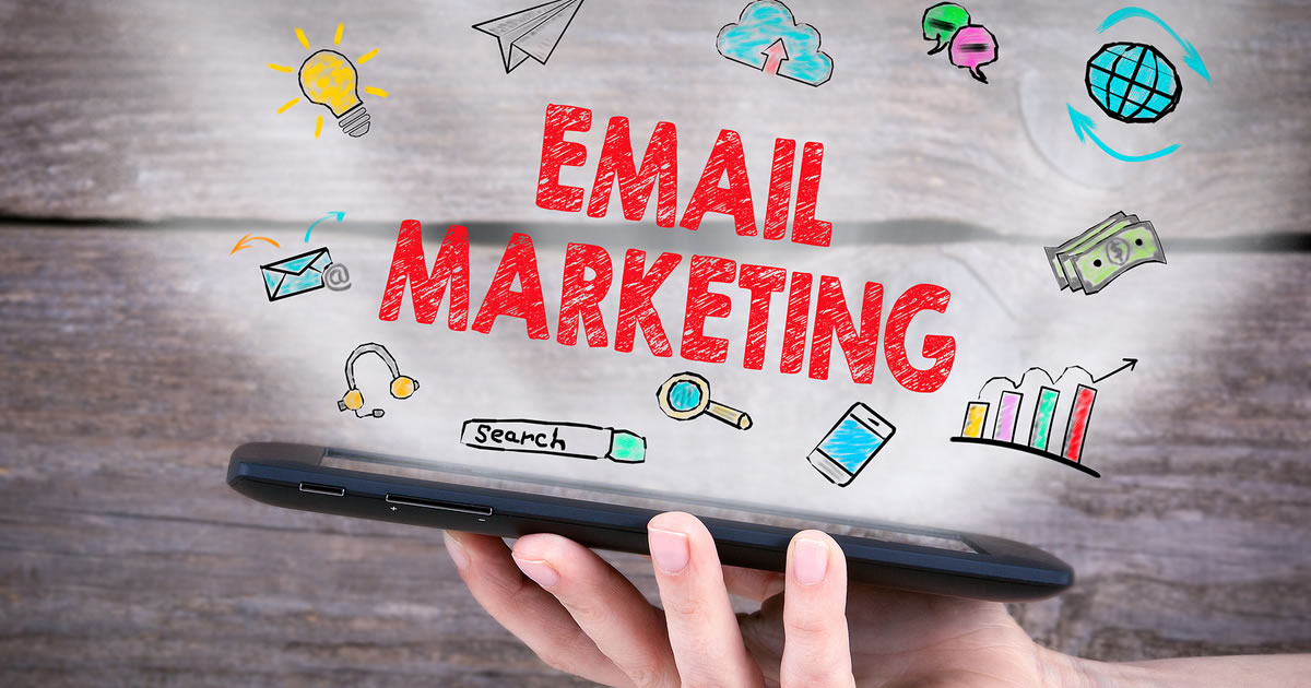 The words email marketing above a hand holding an electronic tablet