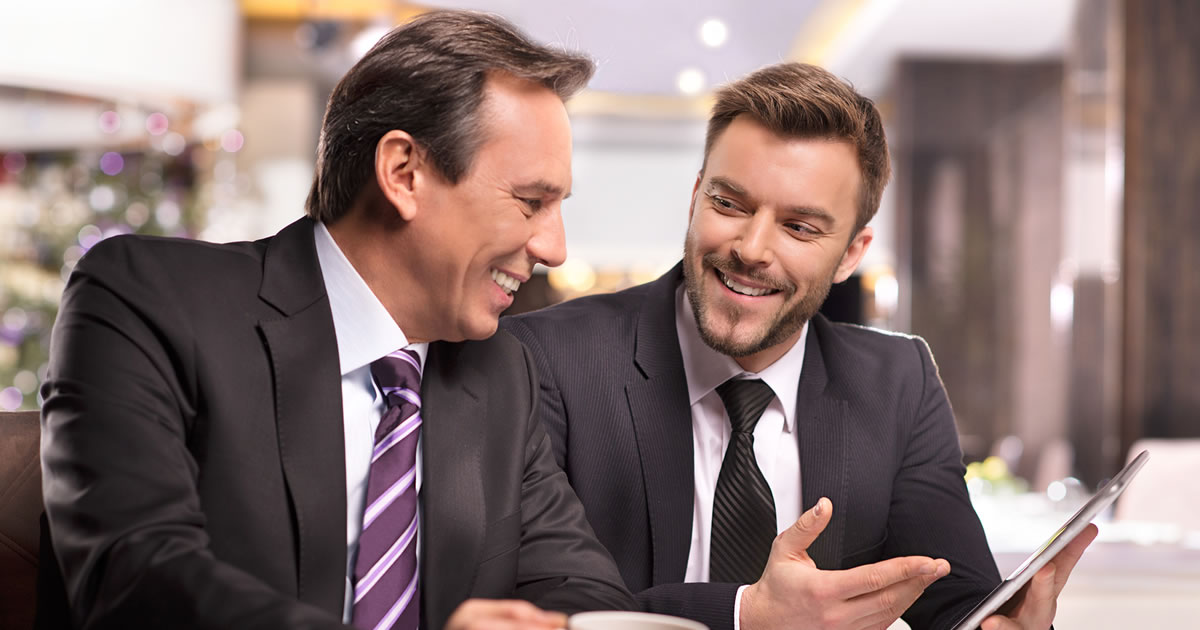 Two smiling businessmen with an electronic tablet