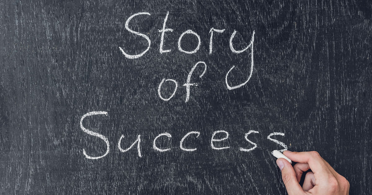 A person's hand holding chalk up to chalkboard that is displaying the words Story of Success