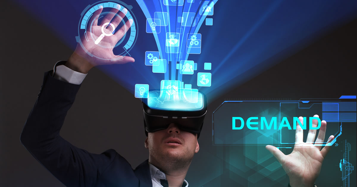 The word demand next to businessman looking in virtual reality device