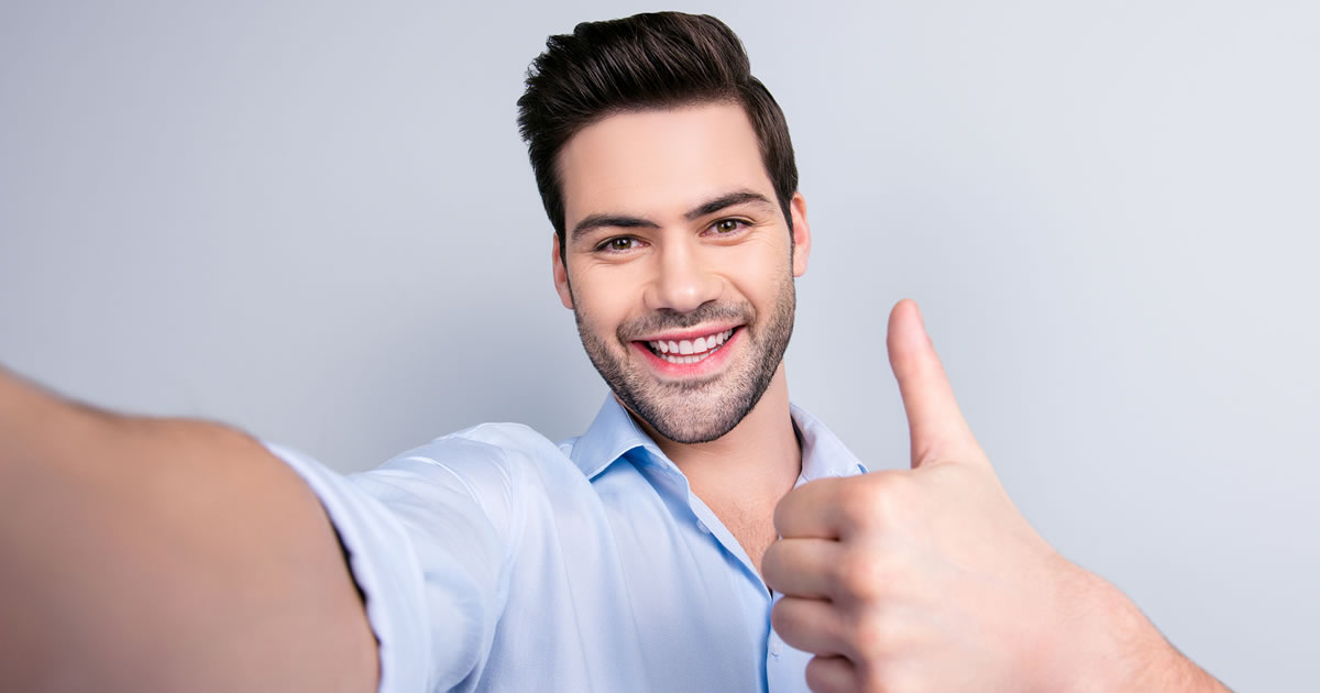 Man smiling and giving thumbs-up while taking a self-porrtait photo