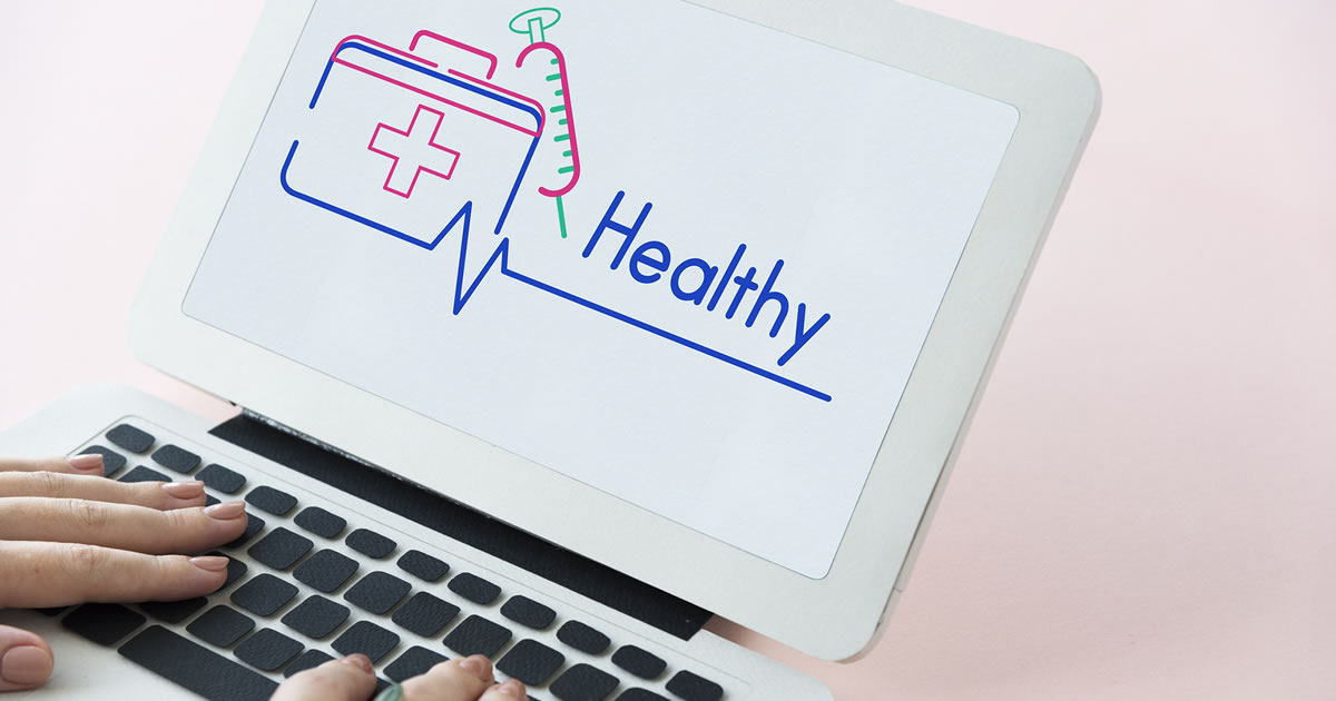 Woman's hands on keyboard of laptop displaying first aid icons and the word healthy onscreen