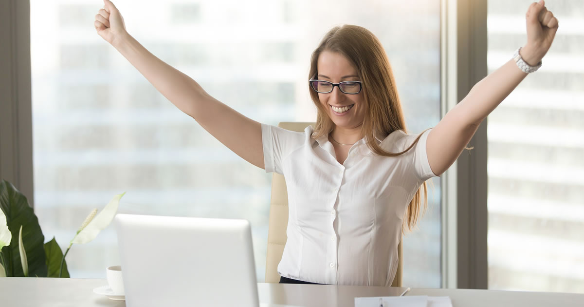 Businesswoman at desk smiling with arms raised triumphantly while looking at laptop