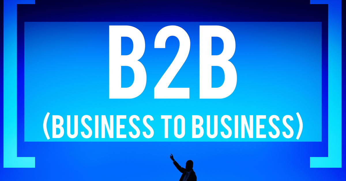 Silhouette of businessman pointing up at words B2B Business to Business