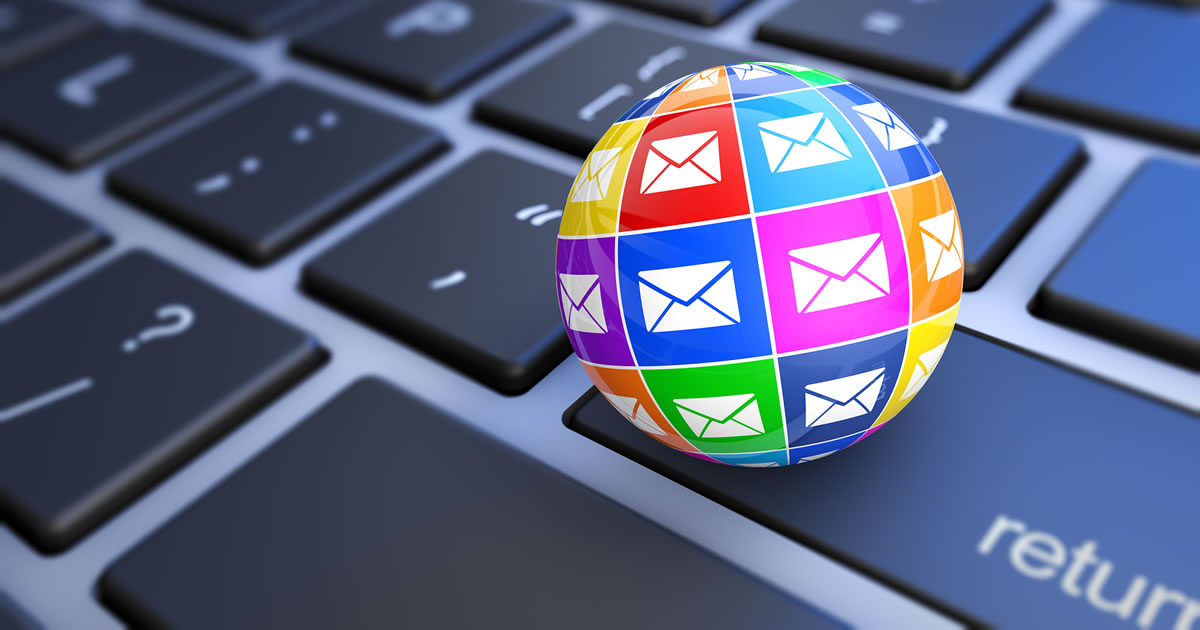 Web and internet email marketing concept with a computer keyboard and a 3D globe covered in colorful email icons.