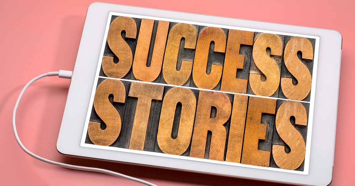 Success stories typography — word abstract in vintage letterpress wood type on a digital tablet