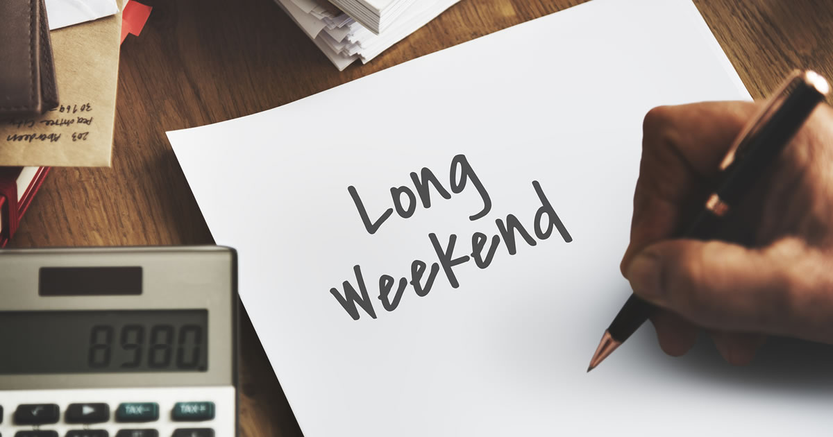 Business entrepreneur writing Long Weekend on a piece of paper