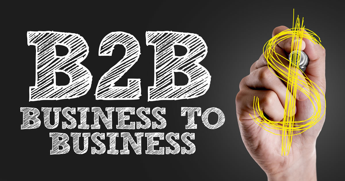 Hand writing a dollar sign next to the text B2B and Business-to-Business
