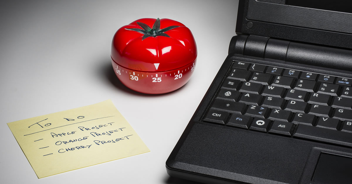 Tomato-shaped kitchen timer set at 25 minutes for Pomodoro technique to encourage focus and fight procrastination in writing