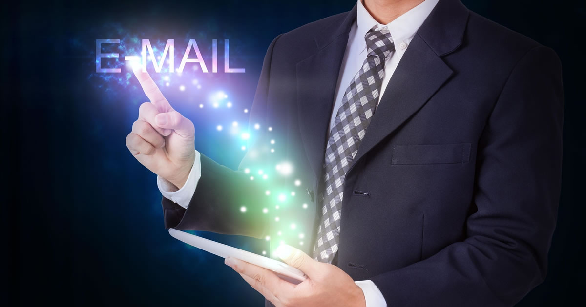 Businessman holding tablet with email icons floating out like magic from the internet connection