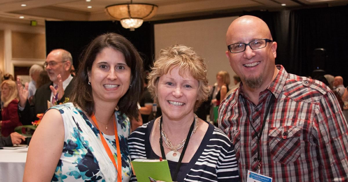 Two female and a male AWAI member smiling and enjoying camaraderie at AWAI's Copywriting Bootcamp