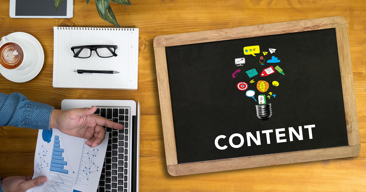 CONTENT CONCEPT Businessman working at desk and using computer pointing to a light bulb labeled with Content