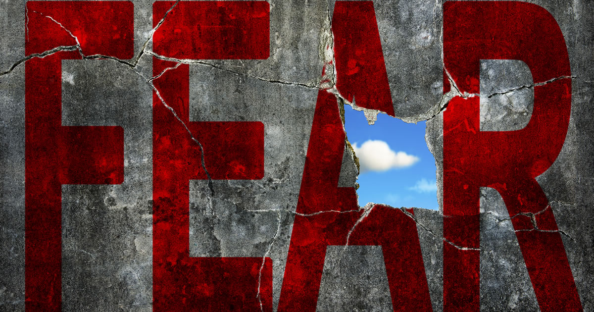 Red word FEAR on grey grunge concrete wall with beautiful blue sky cloud viewed through a big hole in the A in FEAR