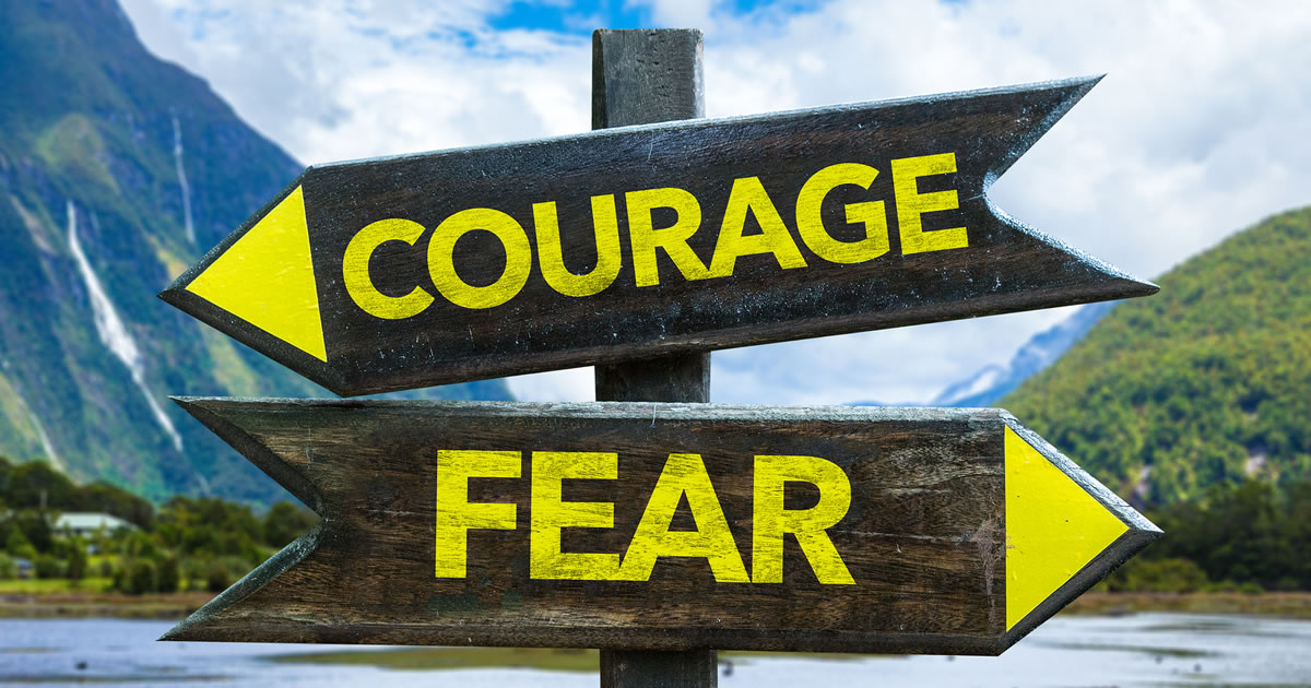 Courage and Fear signposts in a country mountainside area