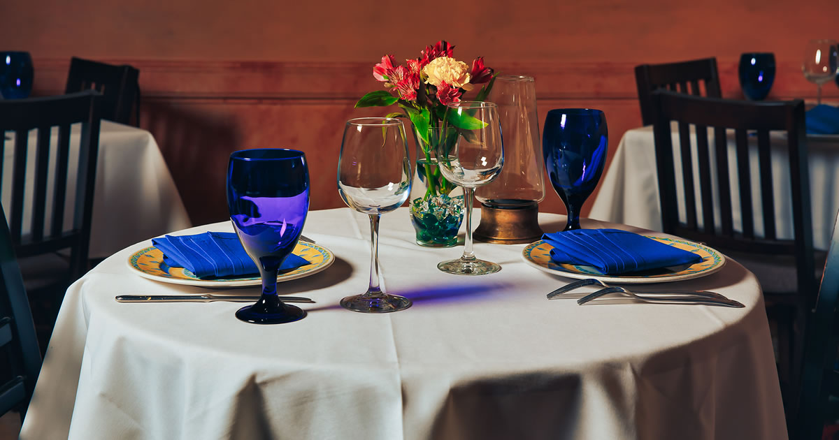 Empty indoor restaurant table set for two with blue glasses, dinnerware, and flowers in a vase