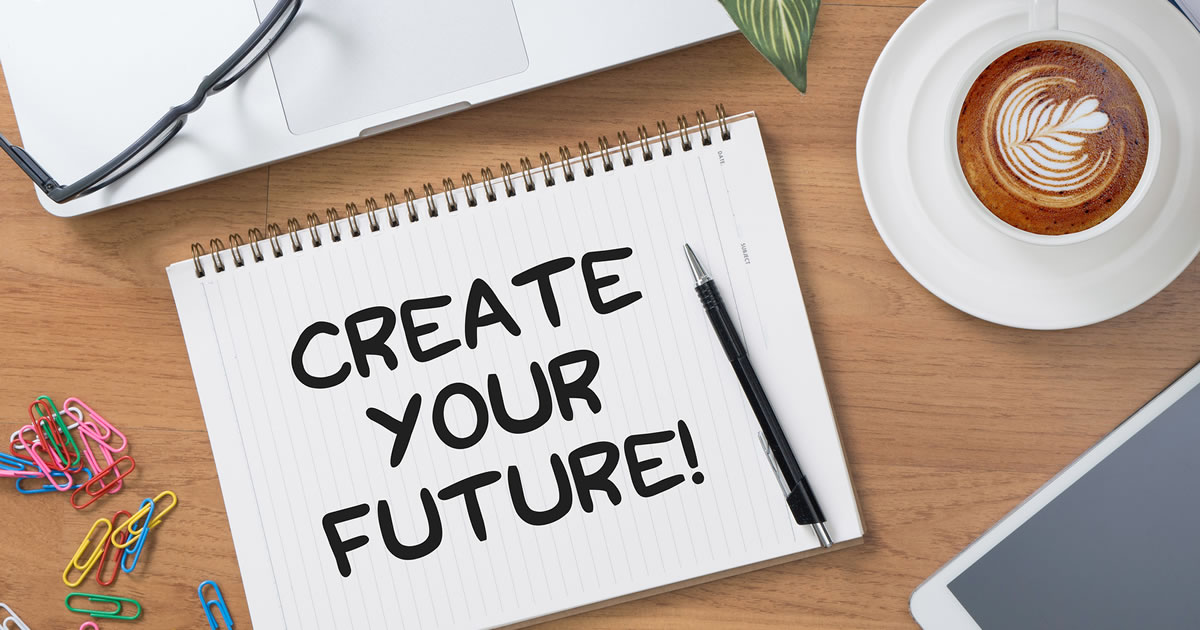 Create Your Future written on tablet on table next to computer keyboard and coffee cup