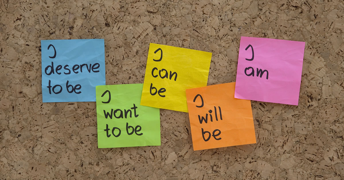 Colorful sticky notes with I deserve to be, I want to be, I can be, I will be, I am, all on bulletin board