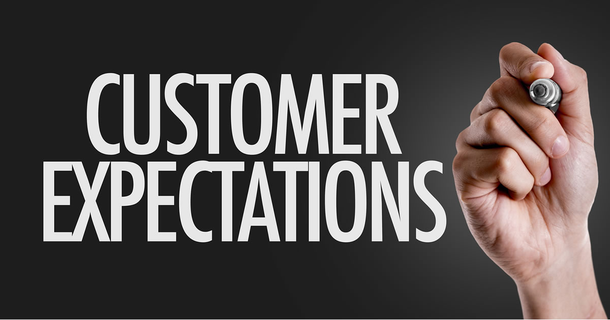 A hand writing the words Customer Expectations