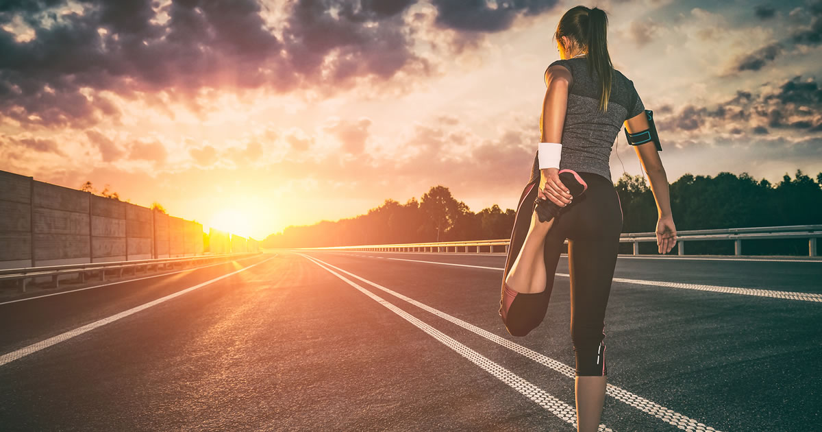 Stretching runner in jogging clothes facing empty road with sun flare in the distance