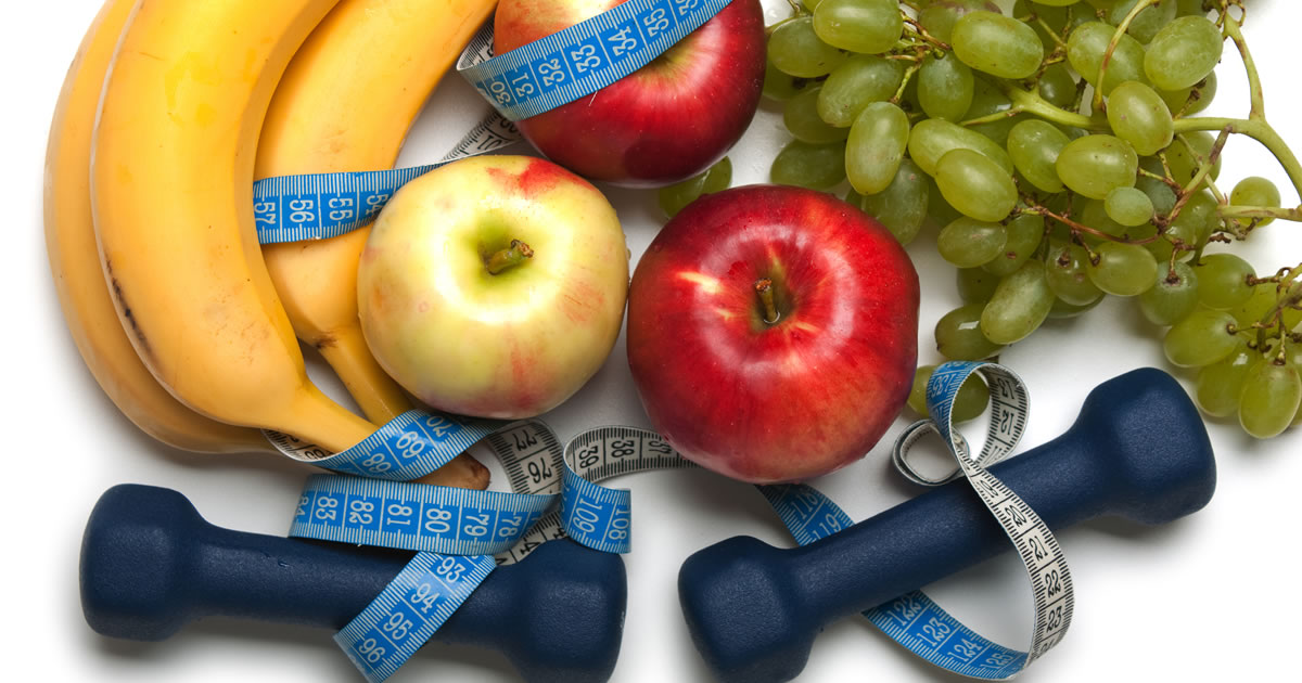 Close-up photo of fruit, exercise hand weights, and a tape measure
