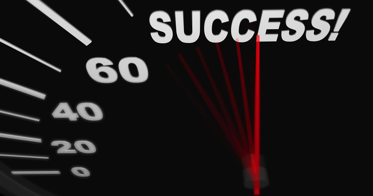 A black automobile speedometer with red needle pushing to the word Success!