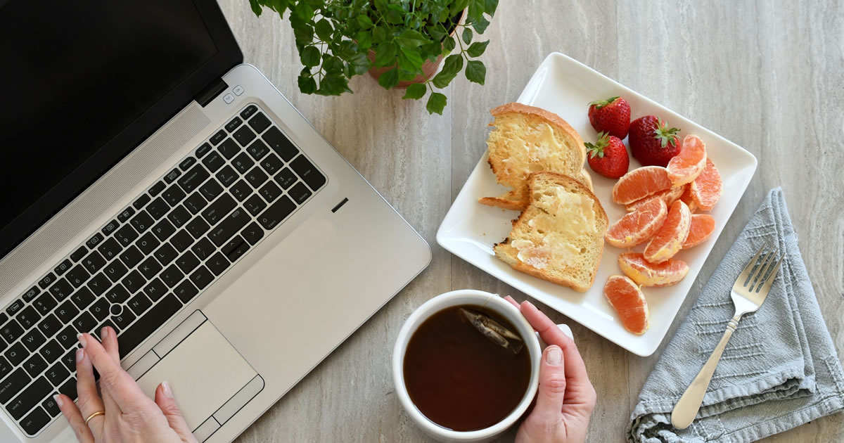 Overhead photo of woman's hands on desk with laptop, tea, toast, and fruit