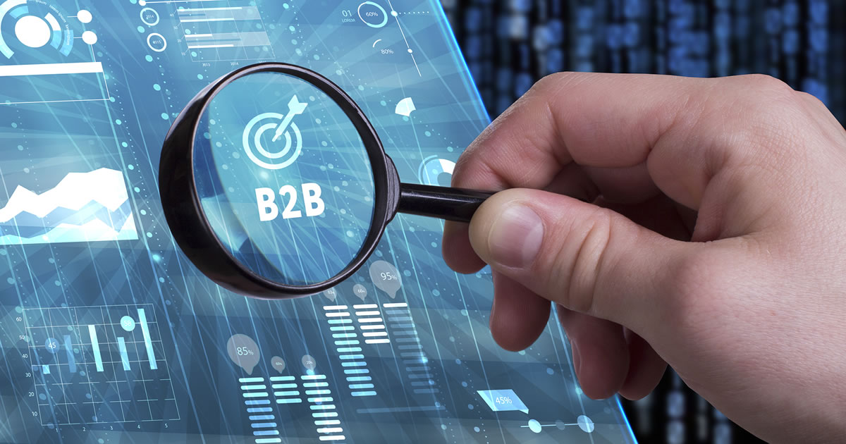 Closeup of a hand holding a magnifying glass in front of a screen showing the text B2B and a target icon