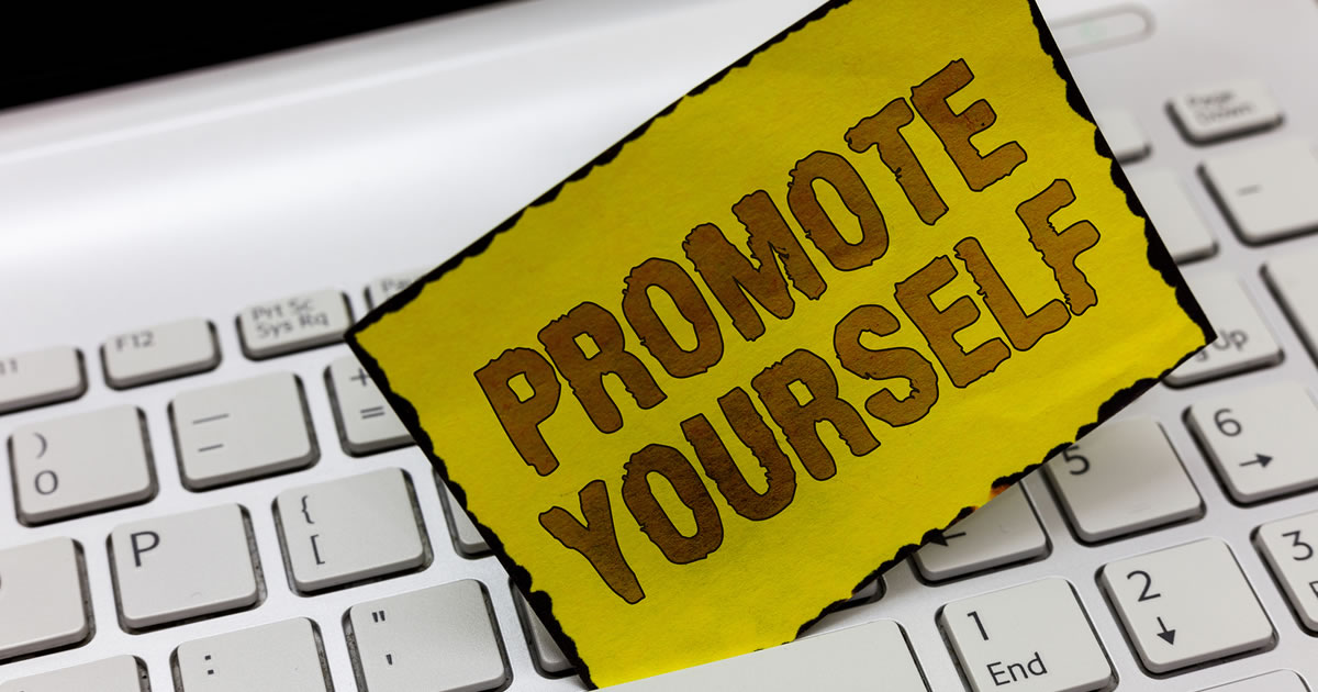 "Written sign reading ""Promote Yourself"" propped up on computer keyboard"