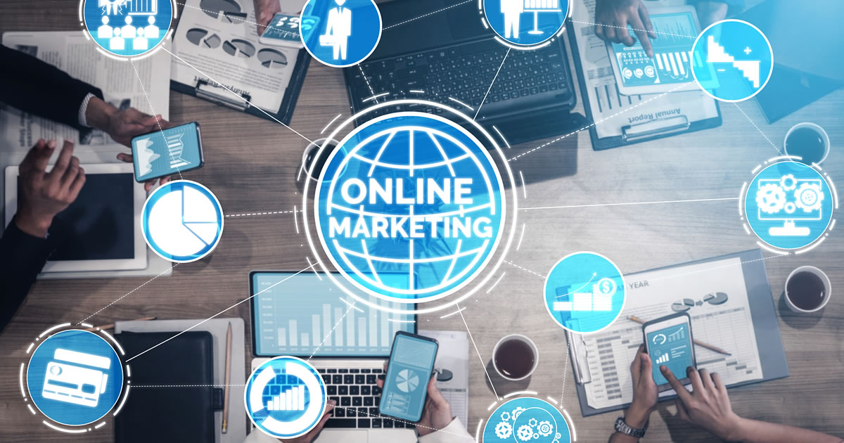 The words Online Marketing surrounded by digital marketing icons over an image of businesspeople using electronic devices