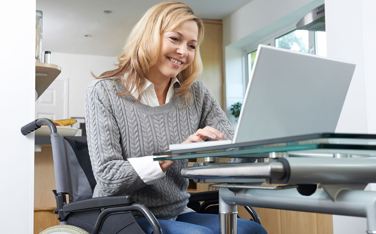 Smiling woman in wheelchair working on laptop at desk at home