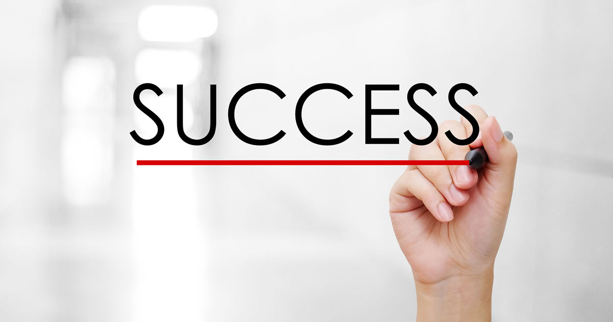 Hand holding a pen underlining the word Success over an out of focus background