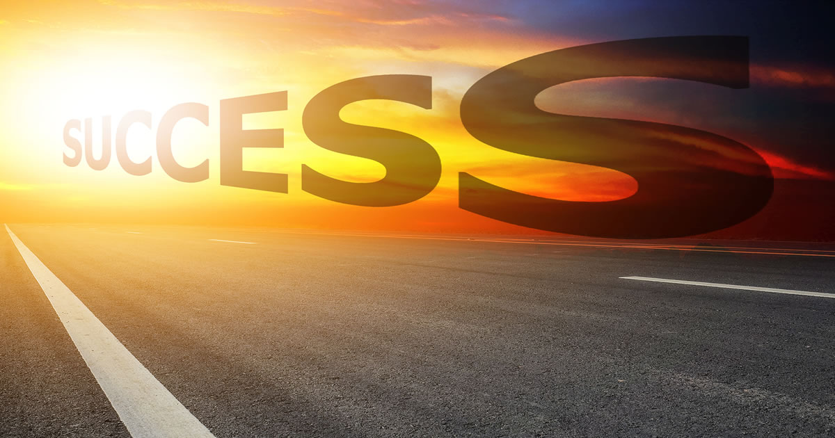 Success written in the sunset sky above an open road; business success concept