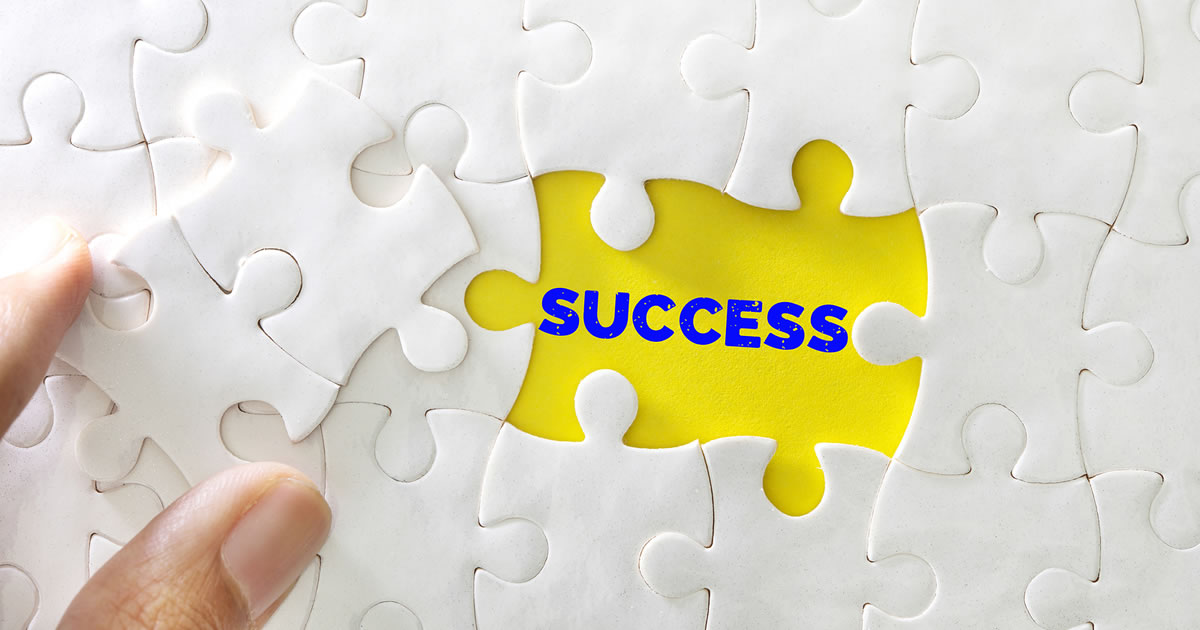 Close up piece of white jigsaw puzzle with SUCCESS text